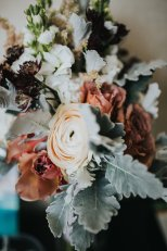 A romantic and vintage style bridal bouquet in blush and mauve with ranunculus, dusty miller, astilbe, and cappuccino roses