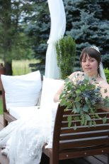 A beautiful bride relaxing on her wedding day. Her unique, but trendy greenery bouquet