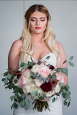 A gorgeous bride and her stunning bridal bouquet in roses, garden roses, protea, ranunculus, and eucalyptus