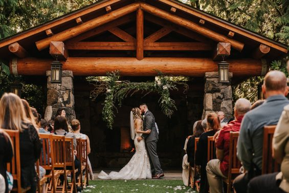 Floral and lush greenery altar installation frame the couple's kiss beautifully