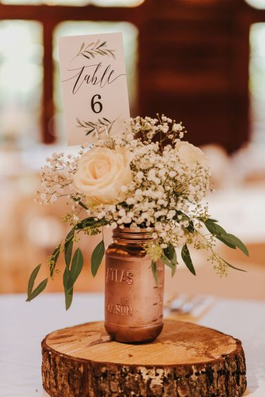 Guest table centerpieces in rose gold, roses, babies breath and eucalyptus