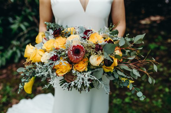 A large lush bridal bouquet in yellows and deep wine palette
