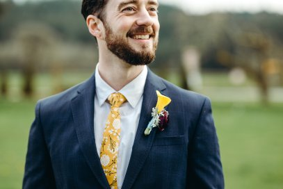 A happy handsome groom with his calla lily and ranunculus boutonniere