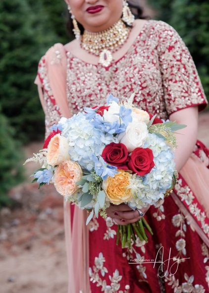 Classic, cluster bride's bouquet in many colors: pale blue hydrangea and delphinium, red roses, juliet David Austin garden roses, astilbe, eucalyptus