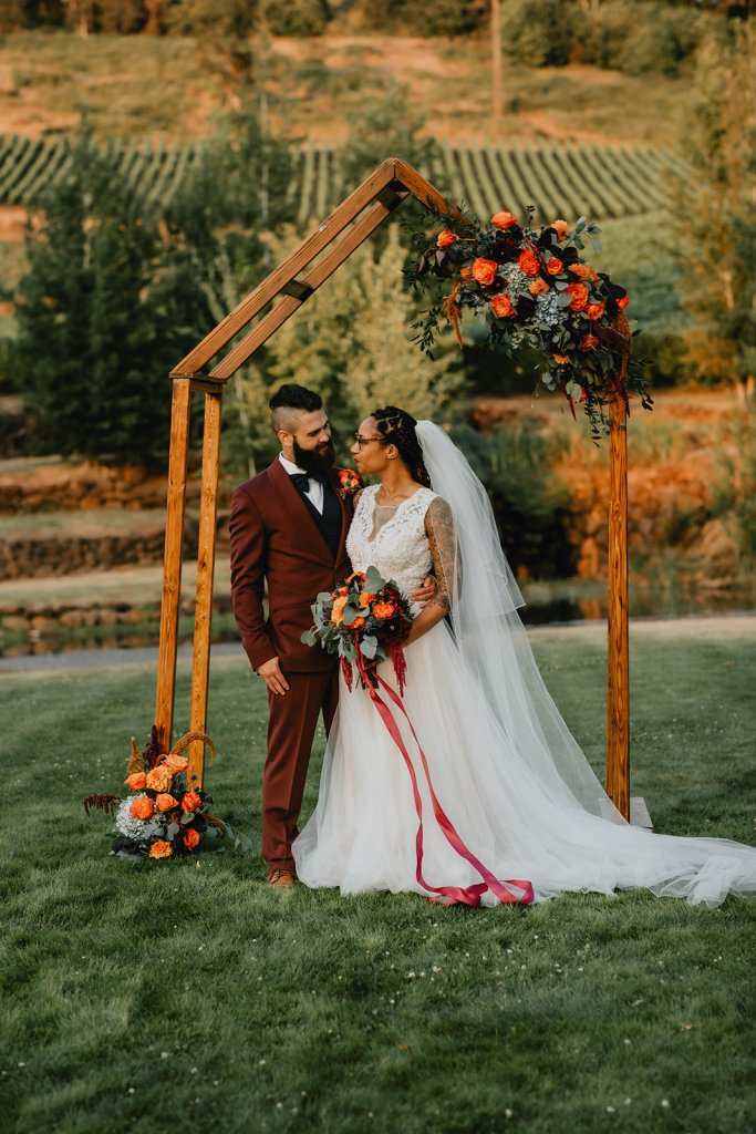wedding arbor, wedding ceremony, outdoor wedding ceremony, oregon florist, oregon wedding florist, portland wedding florist, oregon wedding flowers, ceremony arch, ceremony arbor, fall wedding, autumn wedding colors, fall wedding colors, orange and burgundy flowers, orange and burgundy wedding